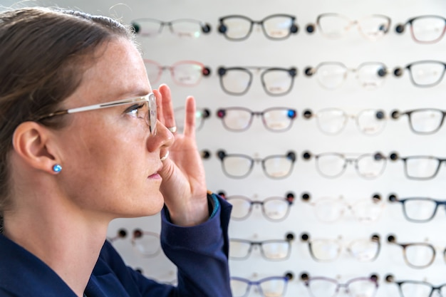 The glasses are selected and tested by a woman in an optics store. copy space