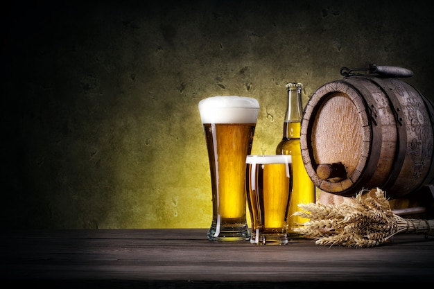 Glasses of beer with bottle and barrel