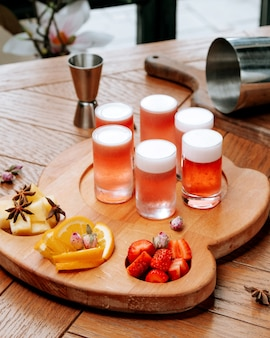 Glasses of beer with froth and sliced fruits on the board