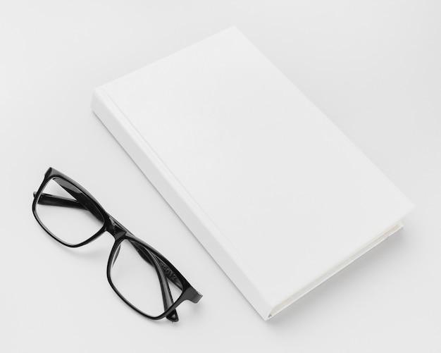 机の上の本の横にあるメガネ