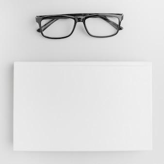 テーブルの上の本の横にあるメガネ