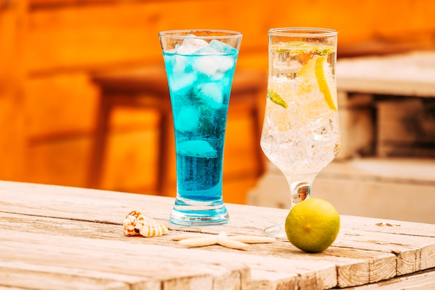 Glasses of blue mint drinks and lime with starfish at wooden table
