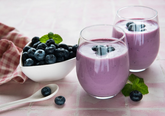 Glasses of blueberry yogurt with blueberries on a pink tile  background.