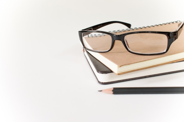 Glasses, book and pencil on white