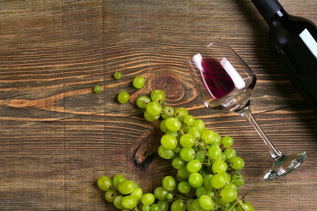Очки бутылка красного вина и винограда на деревянном столе