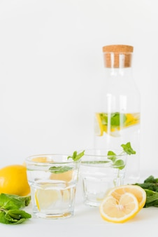 Glasses and bottle with lemon mint drink