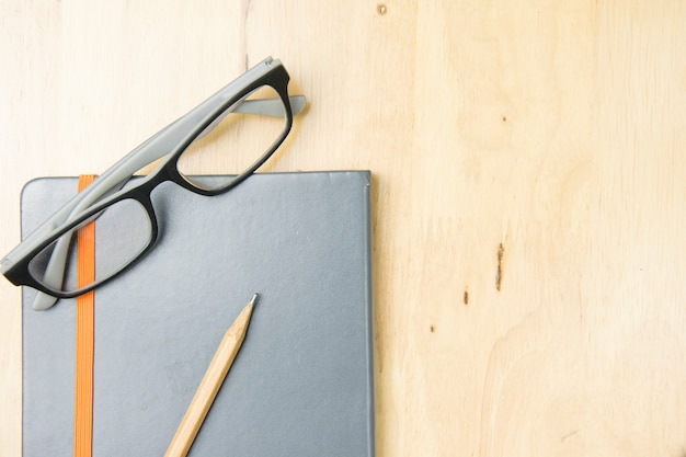 Glasses and brown pencil with notebook on work space wooden. top view, flat lay concept.