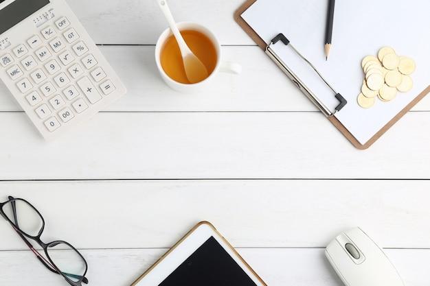Очки, калькулятор, монеты и планшеты на белом аккуратный стол