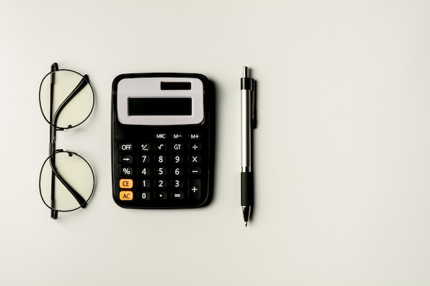 Glasses, calculator and pen. office supplies and education concept.