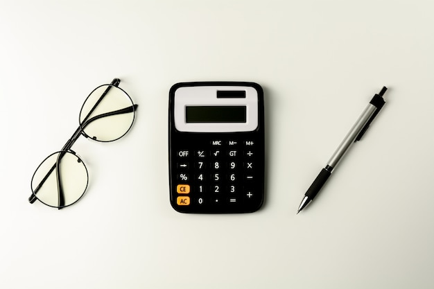Glasses, calculator and pen on white background
