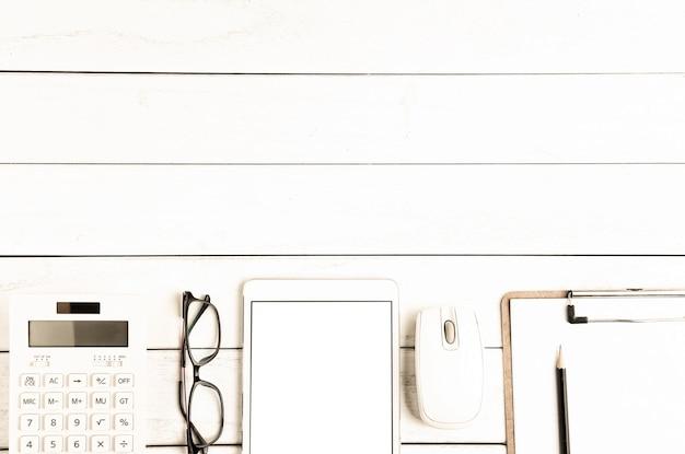 Occhiali, calcolatrice e tavoletta sulla scrivania bianca ordinata
