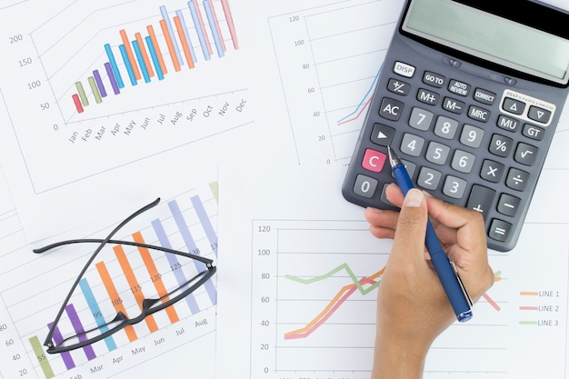 Glasses and calculator with hand holding pen on stock market report