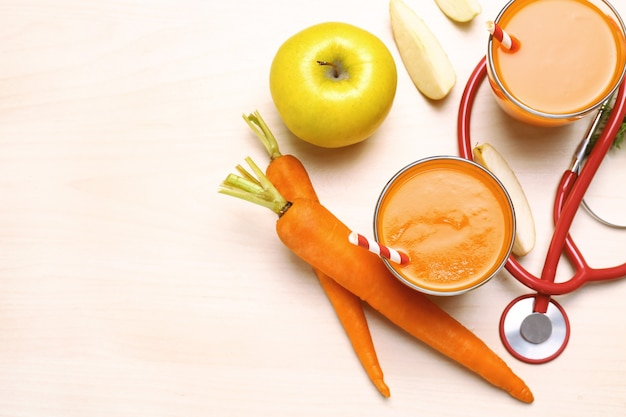 Glasses of carrot juice with fresh apple and stethoscope on the table.
