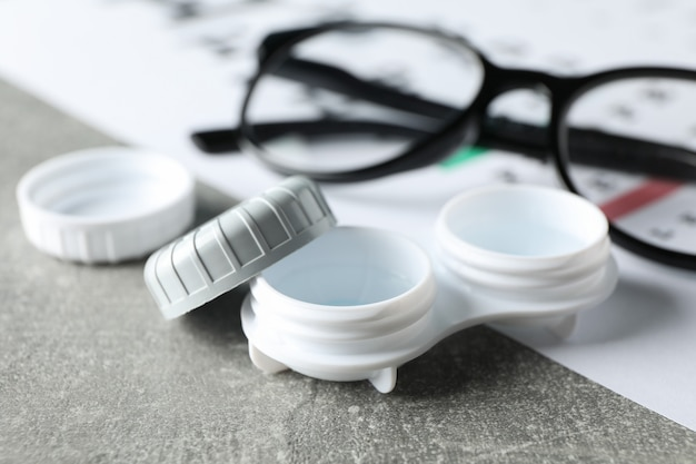 Glasses, case for contact lenses and eye test chart on grey surface, close up