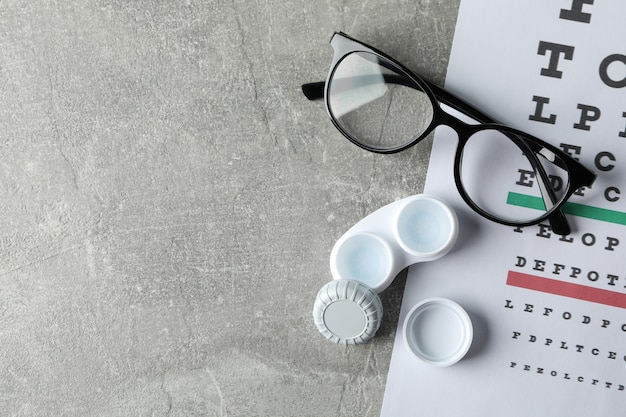 Glasses, case for contact lenses and eye test chart on grey surface, top view