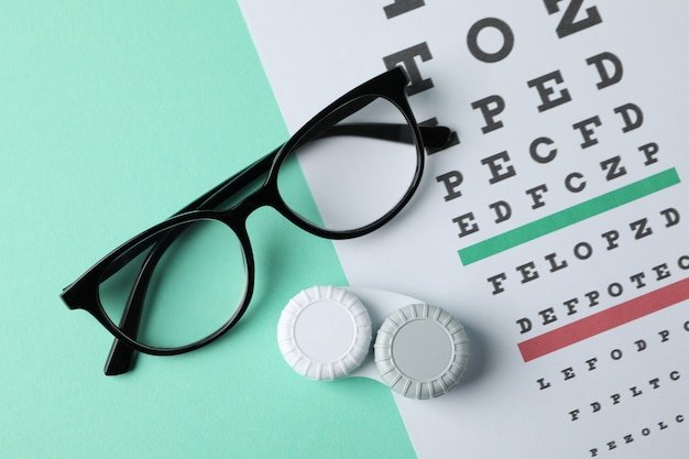 Glasses, case for contact lenses and eye test chart on mint surface, top view