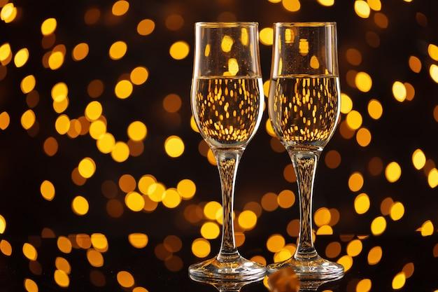 Glasses of champagne against bokeh lights background