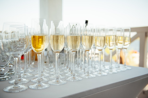 Glasses of champagne at the banquet, white sparkling wine in wine glasses, festive mood.