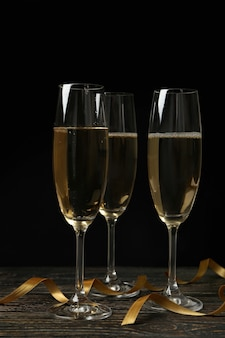Glasses of champagne and curly ribbons on wooden table