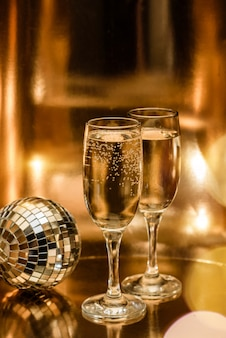 Glasses of champagne and a disco ball on a shining gold surface
