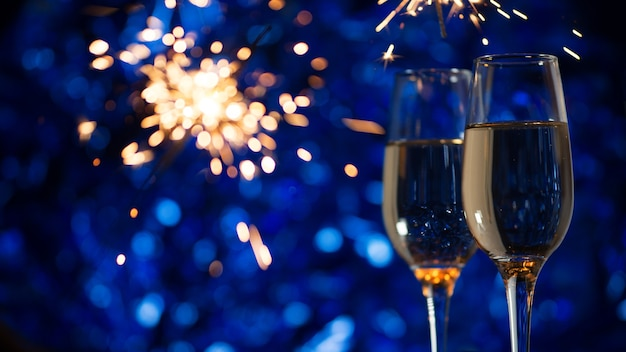 Glasses of champagne on a festive blue decoration with fireworks