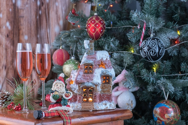 Glasses of champagne and gifts on bright background with fragment of christmas tree and lit up candelabra.