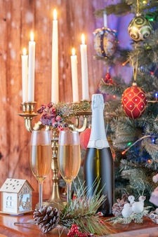Glasses of champagne and gifts composition with lit up candelabra .