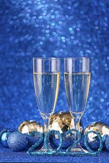 Glasses of champagne and new year decor on shiny blue