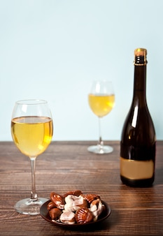 Glasses of champagne or white grape wine with plate of chocolates and bottle on the background on the wooden table.