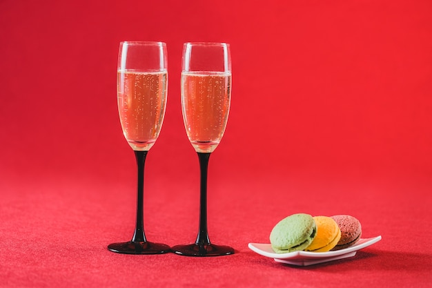 Glasses of champagne with colorful cookies