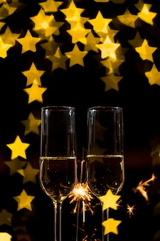 Glasses of champagne with firework and heart-shaped bokeh effect