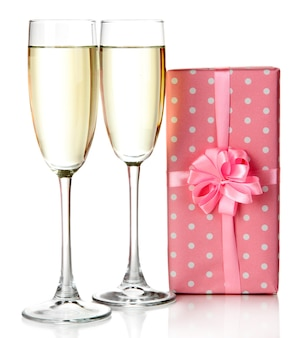 Glasses of champagne with gift box isolated on white