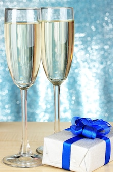 Glasses of champagne with gift box on shiny background