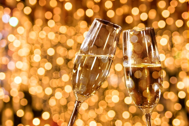 Glasses of champagne with golden bokeh effect