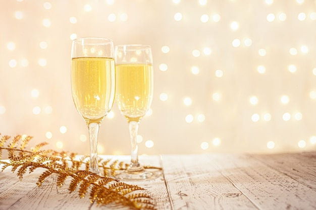 Glasses of champagne on a wooden table with a blurred golden garland, new year's eve concept