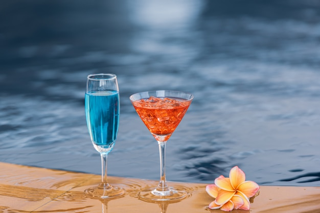 Glasses of cocktail by the swiming pool with flower.