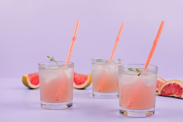 Glasses of cocktail with drinking straws and grapefruits slices on purple background