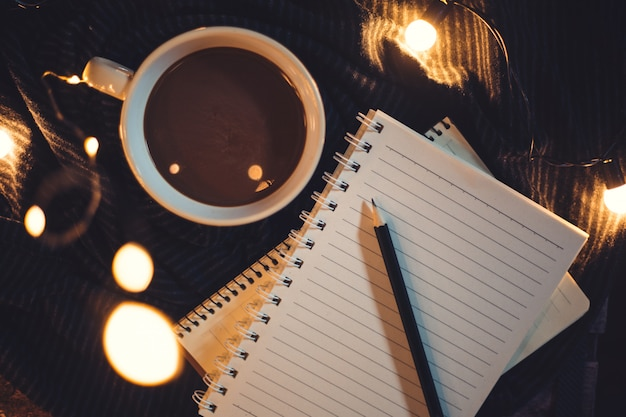 Glasses and coffee are placed on the notebook.