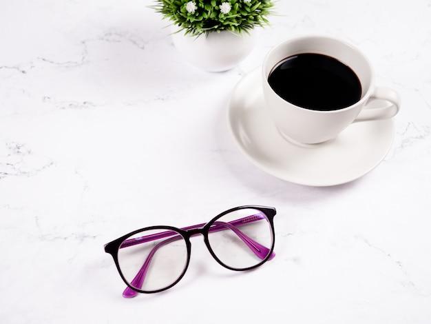 大理石のテーブルの背景に花瓶とグラスコーヒーカップ背景コピースペース朝