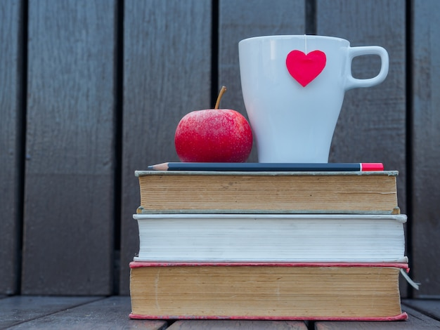 Glasses and coffee white cup with red heart on stack of old books.