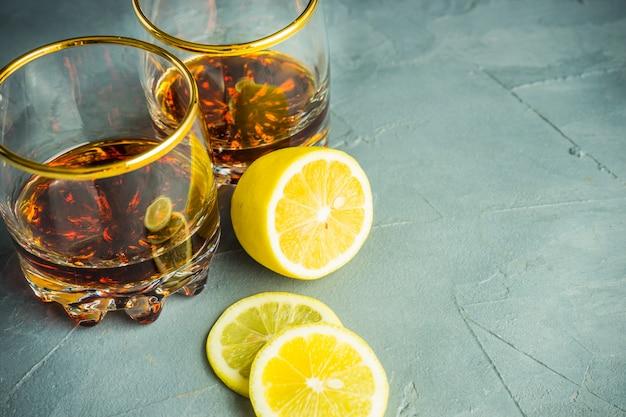 Glasses of cognac and lemon on black stone board