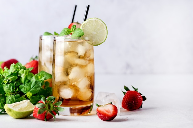 Glasses of cold citrus and strawberry ice tea on light gray background