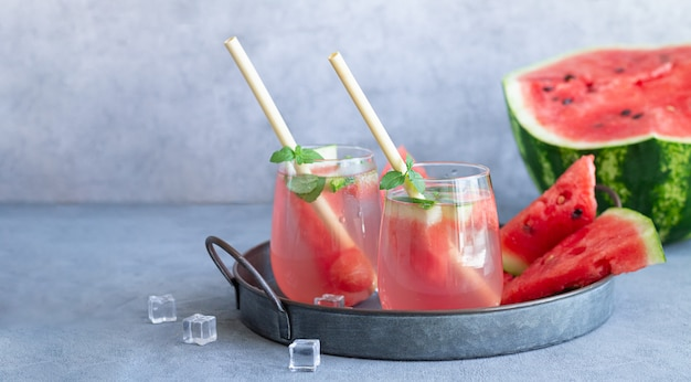Glasses of cold summer drink with watermelon, ice, mint. homemade beverages concept