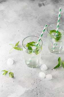 Glasses of cold water with fresh mint leaves and ice cubes on grey concrete