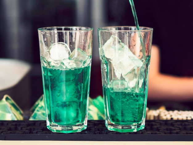 Glasses of colourful green beverage