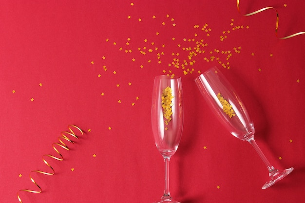 Glasses and confetti on a colored background top view