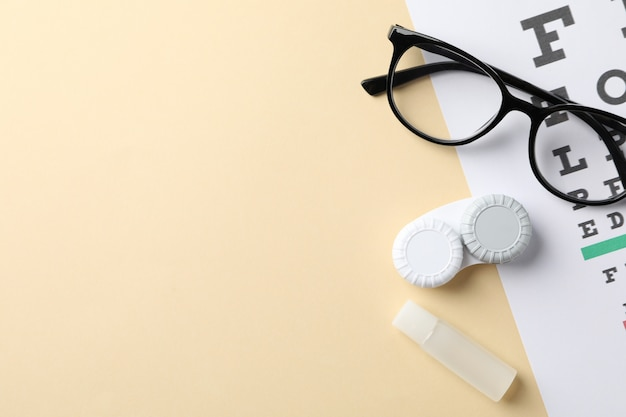 Glasses, contact lenses and eye test chart on beige background, top view