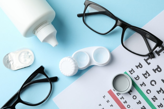 Glasses, contact lenses and eye test chart on blue surface, top view
