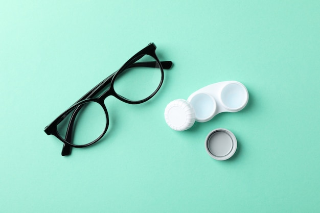 Glasses and contact lenses on mint table, top view