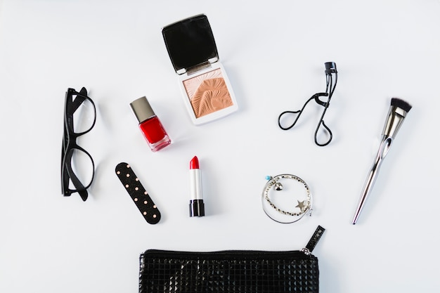 Glasses and cosmetics near stylish makeup bag